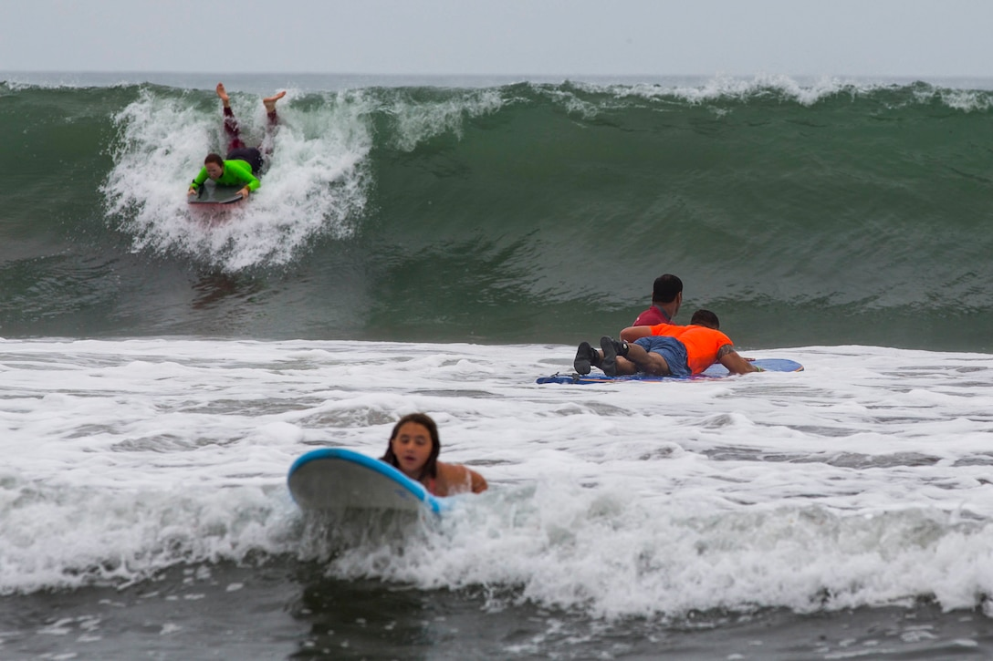 Recovering service members, veterans, volunteers and their loved ones surf during the 12th Annual Operation Amped Surf Camp at San Onofre Beach at Marine Corps Base Camp Pendleton, California, Aug. 18, 2018. Operation Amped holds a surf camp for wounded, ill or injured service members at San Onofre Beach once a year.