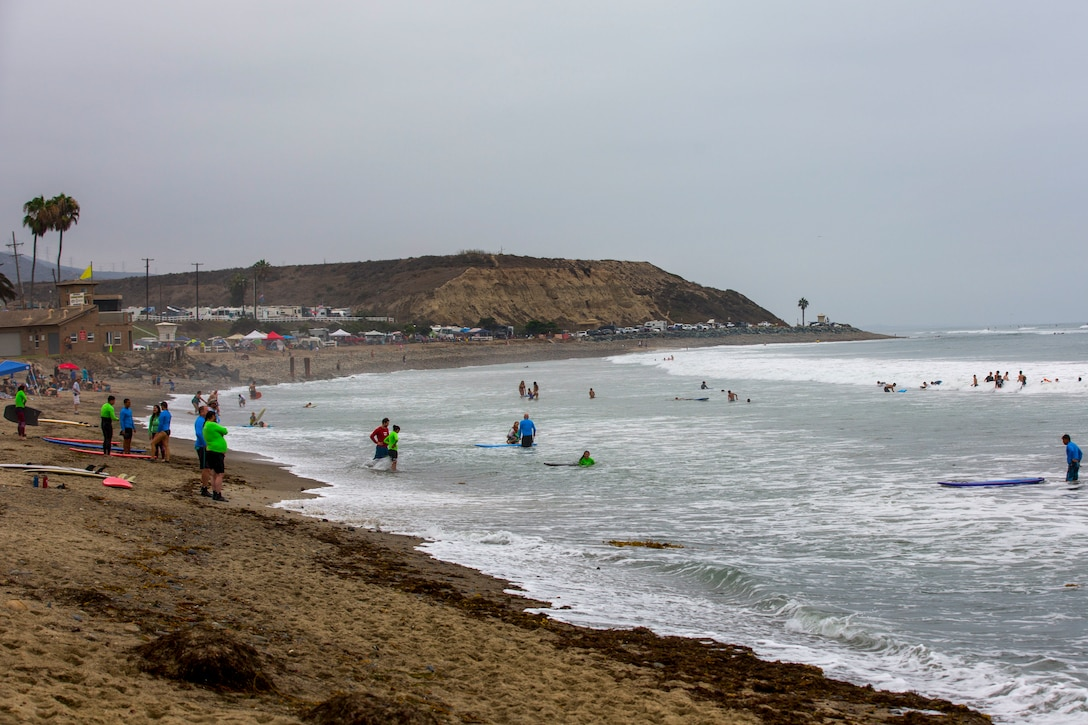Recovering service members, veterans, volunteers and their loved ones prepare to surf during the 12th Annual Operation Amped Surf Camp at San Onofre Beach at Marine Corps Base Camp Pendleton, California, Aug. 18, 2018. Thirteen wounded, ill or injured service members attended the three-day event allowing the wounded warrior community a recreational outlet designed to aid in their recovery.