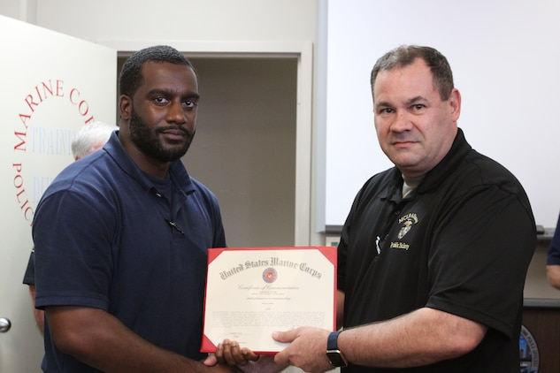 Marine Corps Logistics Base Albany Public Safety Director Paul Ellis (right) presented a certificate of commendation to MCPD officer Willie Hall, (left) August 21. Hall prevented a potential tragedy while responding to a house fire. Hall's dedicated attention to duty, not only saved lives but directly impacted the safety and security of neighboring residents and their families. (U.S. Marine Corps photo by Re-Essa Buckels)