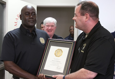 Marine Corps Logistics Base Albany Public Safety Director Paul Ellis (left) presented a 30-year length of service award to MCPD officer Dennis Shedrick (right), August 21. (U.S. Marine Corps photo by Re-Essa Buckels)