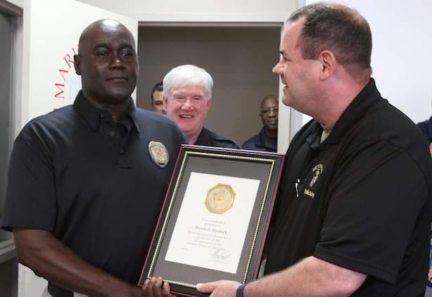 Marine Corps Logistics Base Albany Public Safety Director Paul Ellis (right) presented a 30-year length of service award to MCPD officer Dennis Shedrick (left), August 21. (U.S. Marine Corps photo by Re-Essa Buckels)