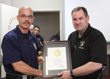 Marine Corps Logistics Base Albany Public Safety Director Paul Ellis (left) presented a 30-year length of service award to MCPD Deputy Chief Sean Lamonzs (right), August 21. (U.S. Marine Corps photo by Re-Essa Buckels)