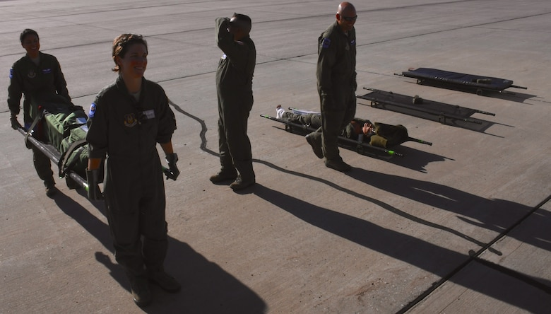 """The 932nd Airlift Wing's, 932nd Aeromedical Evacuation Squadron medical members load up gear for an early morning flight, as shadows stretch across the runway.  Members make final arrangements to carry medical equipment up a ramp, as they work together with ground crew, preparing to fly with """"simulated patients"""" during a training flight, July 21, 2018 at Scott Air Force Base, Ill. The AES trained alongside fellow nurses and medical technicians on a multi day flight aboard a C-130 aircraft visiting from the 910th Airlift Wing of Youngstown, Ohio. The 932nd Airlift Wing is a 22nd Air Force unit, under the Air Force Reserve Command, and is located at Scott Air Force Base, Ill. (U.S. Air Force photos by Lt. Col. Stan Paregien)"""