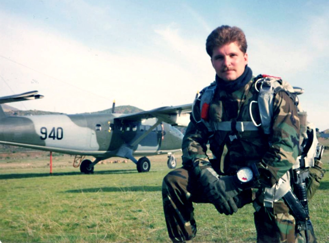 One person kneeling with an aircraft in the background.