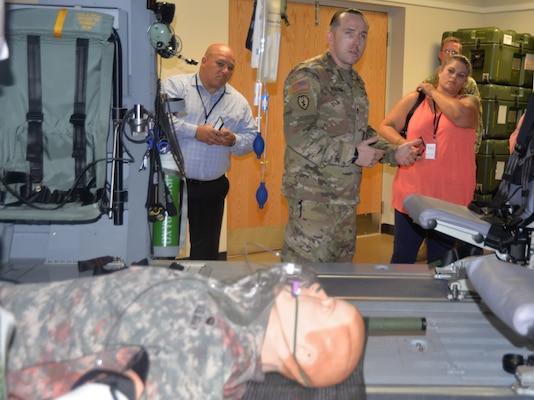 Sgt. 1st Class Lee Hockersmith, U.S. Army Medical Department Center and School instructor and NCO in charge of the Critical Care Flight Paramedic Program at Joint Base San Antonio-Fort Sam Houston, talks to San Antonio community members and civic leaders gathered in a helicopter medical evacuation simulation lab during the Fort Sam Houston Military Medical Tour Aug. 10. The purpose of the tour, a joint effort between Brooke Army Medical Center Public Affairs and the City of San Antonio Office of Military and Veteran Affairs, was to showcase the contributions of military medicine and its impact on the San Antonio community.