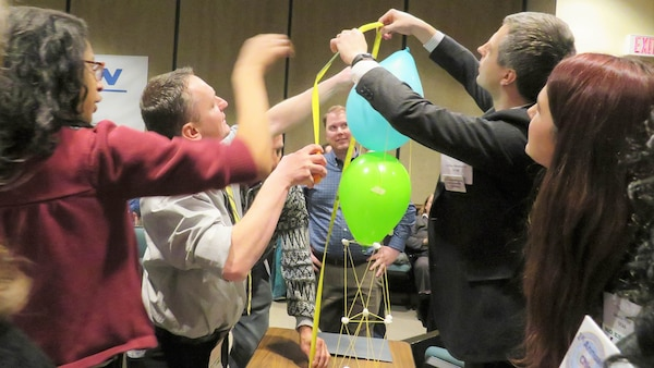 DCMA and DCAA employees build a tower with string and ballons as a team-building exercise.