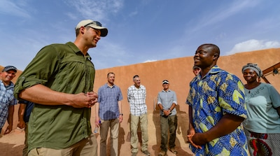 Army Capt. Alexander d'Orchimont, Alpha Company, 411th Civil Affairs Battalion team leader, speaks to a Nigerien orphanage volunteer in Agadez, Niger.