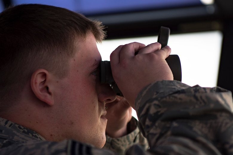 Senior Airman Jonah Sterling, 23d Operations Support Squadron air traffic controller, looks through his binoculars, Aug. 15, 2018, at Moody Air Force Base, Ga. Air traffic controllers direct runway operations by sequencing and separating aircraft, issuing safety alerts, ensuring the safety of pilots and managing the expeditious flow of traffic. (U.S. Air Force photo by Airman Taryn Butler)