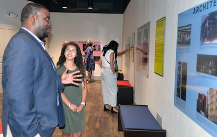 Willie White Jr., Fort Sam Houston Independent School District board of trustees president, talks to Laura DeLeon, a student at Cole High School, as he views one of DeLeon's photos that is displayed in a gallery of photos taken by Cole students during a reception Aug. 9 at the Fort Sam Houston Museum.