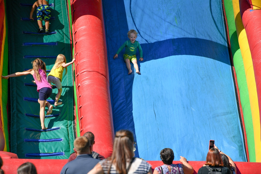 Michael Quinby descends an inflatable slide during the 18th annual Salute Picnic Aug. 17, 2018, at Hill Air Force Base, Utah. Sponsored by the Top of Utah Military Affairs Committee, this year's event included activities such as wet and dry inflatables, a rock climbing wall, face painting and a mechanical bull. (U.S. Air Force photo by R. Nial Bradshaw)
