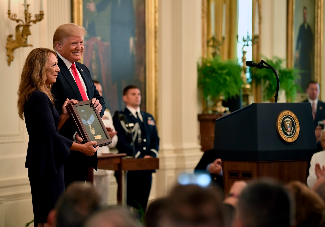 President Donald J. Trump presents the Medal of Honor to Valerie Nessel, the spouse of U.S. Air Force Tech. Sgt. John Chapman, during a ceremony at the White House in Washington, D.C., Aug. 22, 2018. Sergeant Chapman was posthumously awarded the Medal of Honor for actions on Takur Ghar mountain in Afghanistan on March 4, 2002, an elite special operations team was ambushed by the enemy and came under heavy fire from multiple directions. Chapman immediately charged an enemy bunker through thigh-deep snow and killed all enemy occupants. Courageously moving from cover to assault a second machine gun bunker, he was injured by enemy fire. Despite severe wounds, he fought relentlessly, sustaining a violent engagement with multiple enemy personnel before making the ultimate sacrifice. With his last actions he saved the lives of his teammates. (U.S. Air Force photo by Wayne A. Clark)