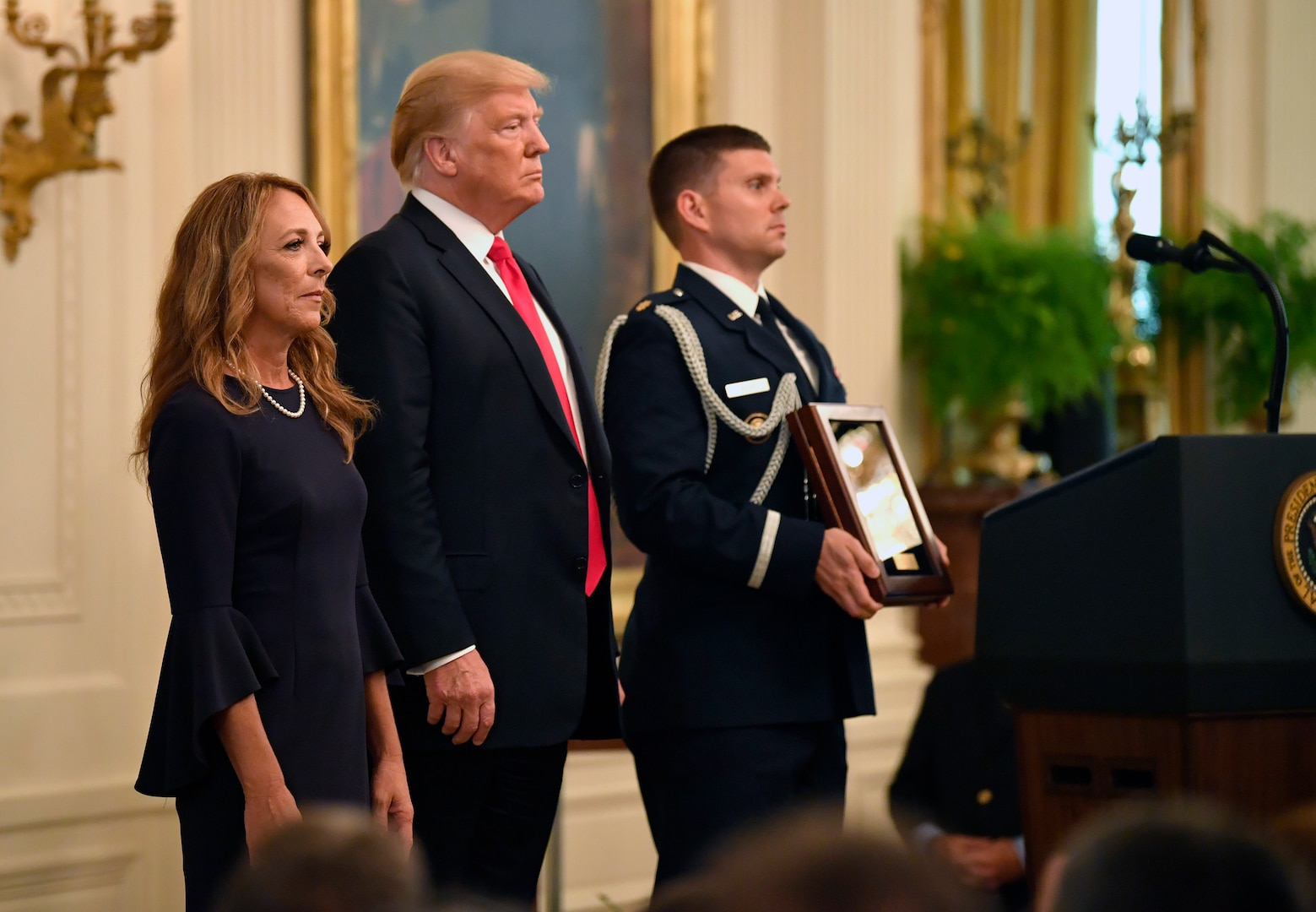 Valerie Nessel, the spouse of Tech. Sgt. John Chapman, stands as the citation is read before receiving the Medal of Honor from President Donald J. Trump during a ceremony at the White House in Washington, D.C., Aug. 22, 2018. Chapman was posthumously awarded the Medal of Honor for actions on Takur Ghar mountain in Afghanistan on March 4, 2002, when his elite special operations team was ambushed by the enemy and came under heavy fire from multiple directions. Chapman immediately charged an enemy bunker through thigh-deep snow and killed all enemy occupants. Courageously moving from cover to assault a second machine gun bunker, he was injured by enemy fire. Despite severe wounds, he fought relentlessly, sustaining a violent engagement with multiple enemy personnel before making the ultimate sacrifice. With his last actions, he saved the lives of his teammates. (U.S. Air Force photo by Wayne A. Clark)