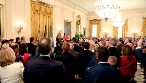 Attendees observe as President Donald J. Trump presents the Medal of Honor to Valerie Nessel, the spouse of U.S. Air Force Tech. Sgt. John Chapman, during a ceremony at the White House in Washington, D.C., June 26, 2018. Chapman was posthumously awarded the Medal of Honor for actions on Takur Ghar mountain in Afghanistan on March 4, 2002, when his elite special operations team was ambushed by the enemy and came under heavy fire from multiple directions. Chapman immediately charged an enemy bunker through thigh-deep snow and killed all enemy occupants. Courageously moving from cover to assault a second machine gun bunker, he was injured by enemy fire. Despite severe wounds, he fought relentlessly, sustaining a violent engagement with multiple enemy personnel before making the ultimate sacrifice. With his last actions, he saved the lives of his teammates. (U.S. Air Force photo by Wayne A. Clark)