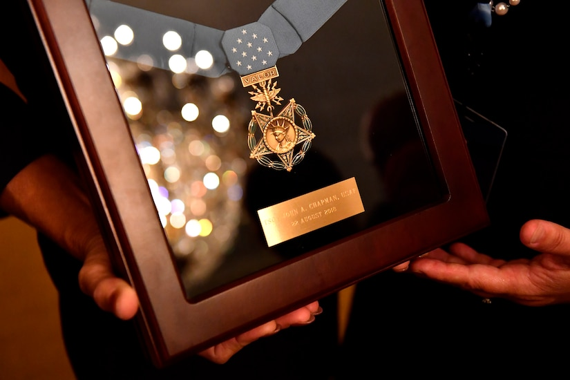 Valerie Nessel, the spouse of U.S. Air Force Tech. Sgt. John Chapman, holds up the Medal of Honor after receiving it from President Donald J. Trump during a ceremony at the White House in Washington, D.C., Aug. 22, 2018. Chapman was posthumously awarded the Medal of Honor for actions on Takur Ghar mountain in Afghanistan on March 4, 2002. His elite special operations team was ambushed by the enemy and came under heavy fire from multiple directions. Chapman immediately charged an enemy bunker through thigh-deep snow and killed all enemy occupants. Courageously moving from cover to assault a second machine gun bunker, he was injured by enemy fire. Despite severe wounds, he fought relentlessly, sustaining a violent engagement with multiple enemy personnel before making the ultimate sacrifice. With his last actions, he saved the lives of his teammates. (U.S. Air Force photo by Staff Sgt. Rusty Frank)