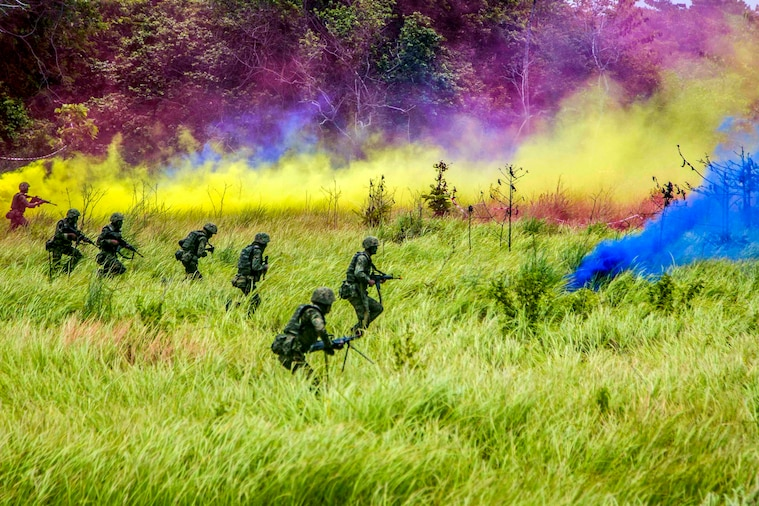 Soldiers advance through a field under cover of smoke.