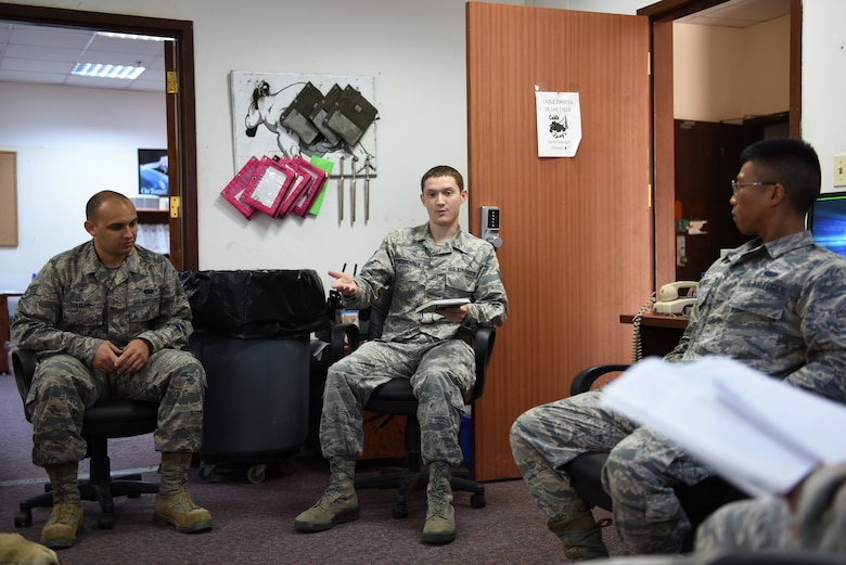 Members of the communication squadron brief each other on workplace safety