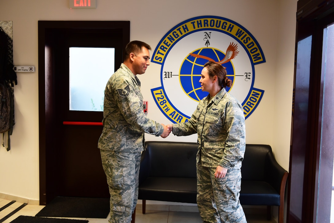 An MXS Airman receives a coin from a Safety officer