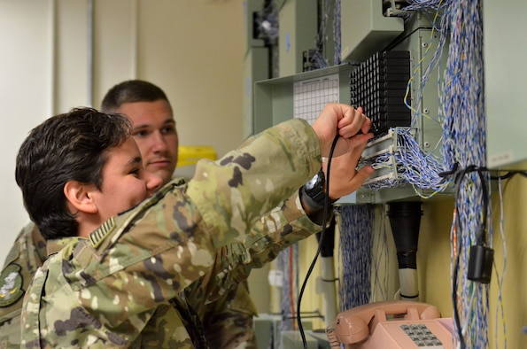 Airman 1st Class Courtney Sherman and Airman 1st Class Tyler Elam, cyber transport technicians assigned to the 609th Expeditionary Air Communications Squadron (EACOMS), check the functionality of phone lines Aug. 8, 2018, at Al Udeid Air Base, Qatar. The 609th EACOMS provides the sole communication support to the Combined Air Operations Center, which is responsible for planning and executing air operations in support of U.S. Central Command (CENTCOM) military objectives in the CENTCOM area of responsibility. (U.S. Air Force photo by Staff Sgt. Caitlin Conner)