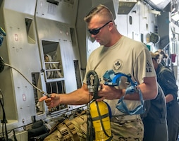 Tech. Sgt. Tyler Port, 911th Aeromedical Evacuation Squadron, Pittsburgh ARS, Pa., sets up emergency oxygen gear for AES Airman aboard the C-17.  (Air Force Photo/Paul Zadach)