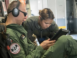 Capt. Marcin Kunicki, Polish Air Force, and 1st Lt. Laura Maldonado, 433rd AES, Lackland AFB, Texas, review a checklist for setting up the AES equipment.
