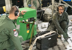 Capt. Marcin Kunicki and 1st Lt. Kay McAmis, 34th AES, Peterson AFB, Colo., secure life support equipment in the C-17 before takeoff.(Air Force Photo/Paul Zadach)