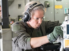 Capt. Tiffany Prochaska, 81st Medical Group, Keesler AFB, Miss., makes some final adjustments to the life support equipment used by the CCATT. (Air Force Photo/Paul Zadach)
