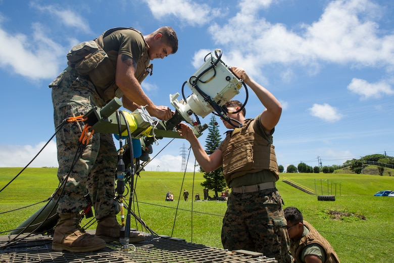Lance Cpl. Justin Simmons, left, and Lance Cpl. Austin Ruckle, right, both field radio operators with 7th Communication Battalion, III Marine Expeditionary Force Information Group remove the free space optic system from a tactical elevated antenna mass at Camp Hansen, Okinawa, Japan, Aug. 17, 2018. Marines are testing the new system, which will allow Marines to transmit mission critical information faster and more securely in environments with damaged infrastructure.