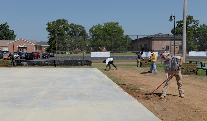 """Contracted construction workers place turf around the Alpha Warrior concrete pad Aug. 13, 2018, on Columbus Air Force Base, Mississippi. Alpha Warrior designs state-of-the-art workout stations called battle rigs or battle stations, similar to the well-known """"American Ninja Warrior"""" obstacle courses. (U.S. Air Force photo by Airman Hannah Bean)"""