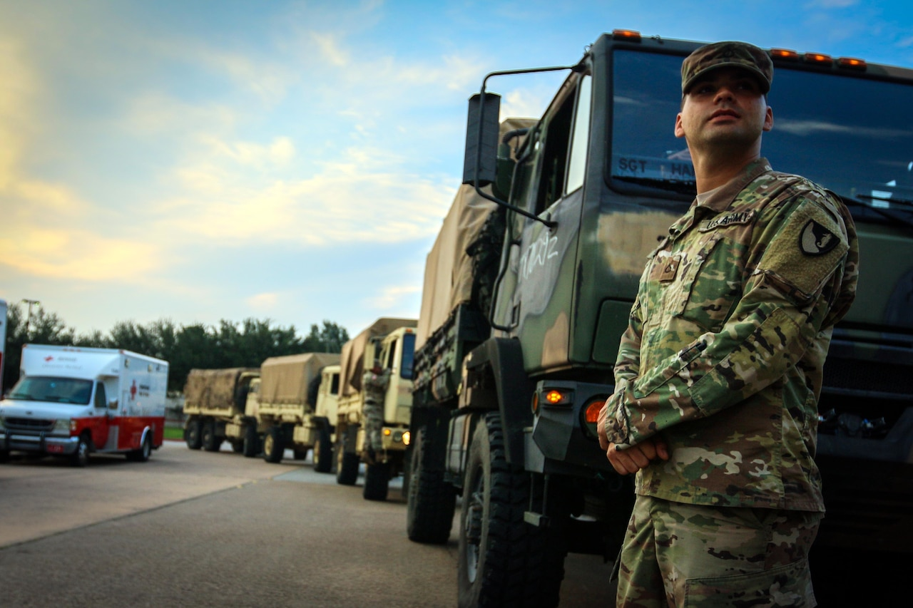 Soldier stands by military truck.