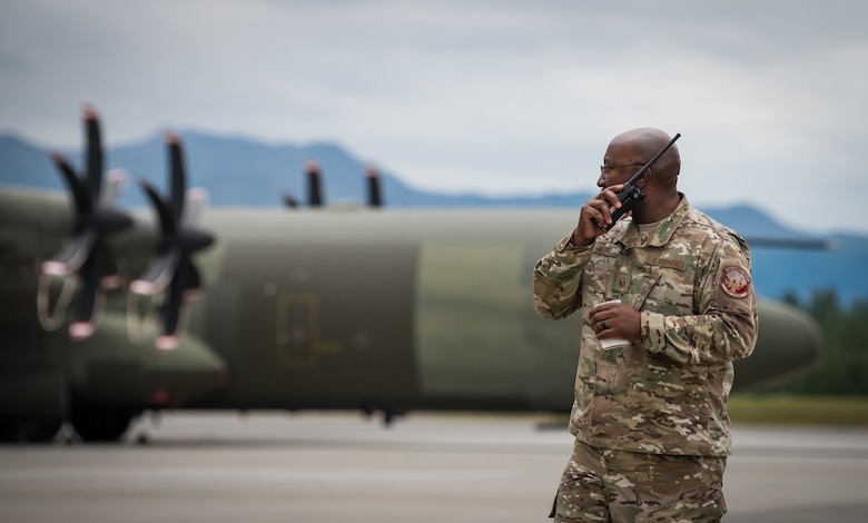 U.S. Air Force Master Sgt. Rick Moore, 353rd Special Operations Maintenance Squadron productions superintendent, speaks on a walkie-talkie at Joint Base Elmendorf-Richardson, Alaska, Aug. 13, 2018. In addition to U.S. Air Force Airmen, counterparts from Australia, Canada and the United Kingdom are also scheduled to participate, enabling the exchange of tactics, techniques and procedures while improving interoperability with fellow Airmen.