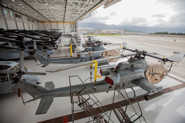 Marine helicopters are lined up in a hangar.
