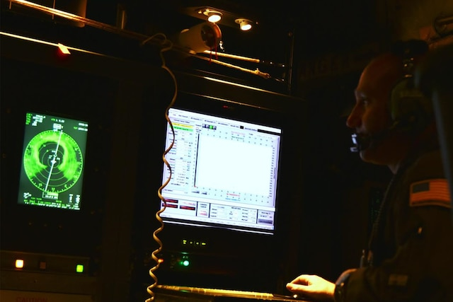 An airman reads data from weather monitoring equipment.