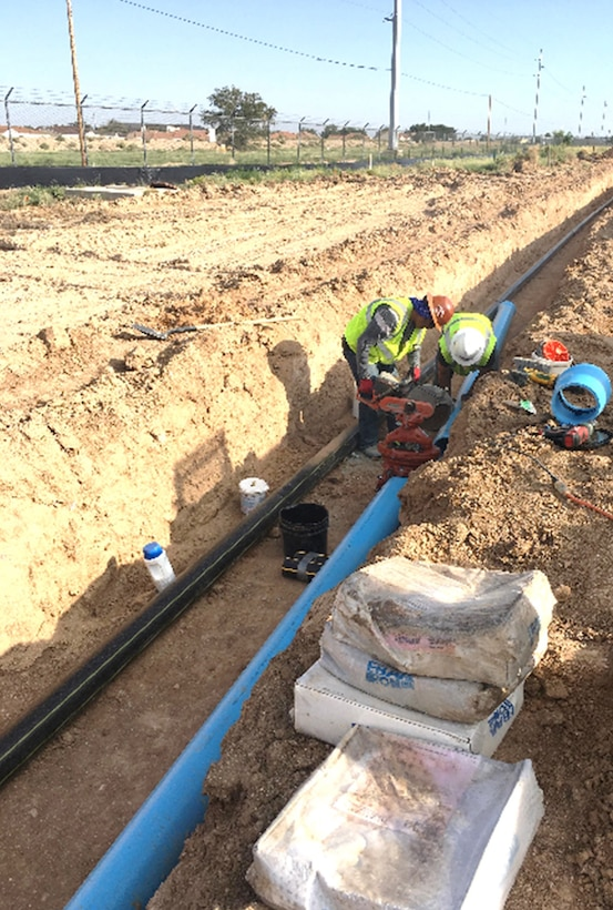 ROTC Cadet Robert Thomas (right) gets a first-hand look at the installation of gas and water utilities for the NNSA Albuquerque Complex Project, Aug. 6, 2018.