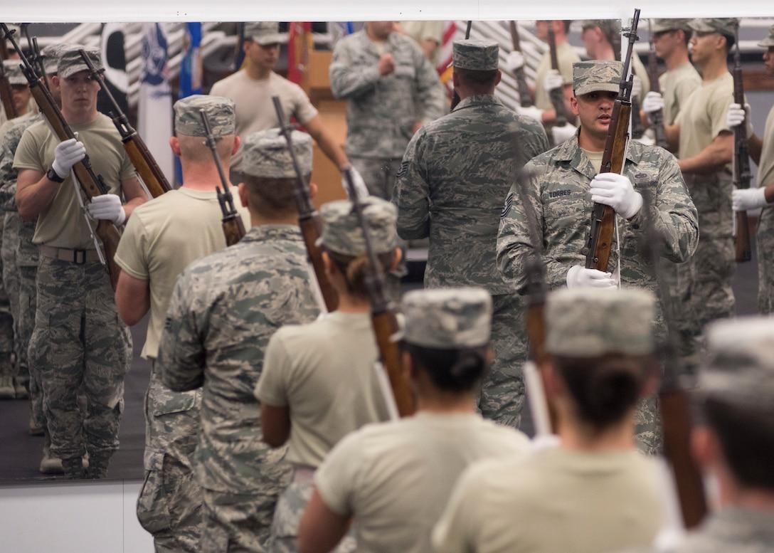 Base Honor Guard trainees synchronize rifle movements at Fairchild Air Force Base, Washington, Aug. 1, 2018. Honor Guard consists of 21 members, plus instructors, divided into three flights: Alpha, Bravo and Charlie flights. (U.S. Air Force photo/Senior Airman Ryan Lackey)