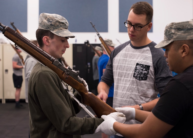 SSgt. Brian Kamphaus, 92nd Air Refueling Wing NCO In-charge of base Honor Guard, helps a trainee adjust his hands during rifle bearing practice at Fairchild Air Force Base, Aug. 4, 2018. The NCO in-charge position of the Honor Guard flight is a two-year long posting, with the former leader working hands-on to train new leadership. (U.S. Air Force photo/Senior Airman Ryan Lackey)