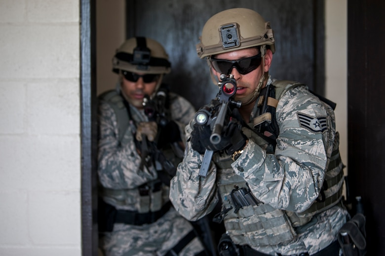 U.S. Air Force Staff Sgt. Kevin Gonzalez, an emergency services team (EST) member and Tech. Sgt. Melvin Santos, an EST leader, both assigned to the 6th Security Forces Squadron (SFS), breach a door in a simulator house at MacDill Air Force Base, Fla., Aug. 22, 2018.