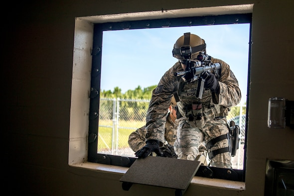 U.S. Air Force Tech. Sgt. Melvin Santos, an emergency services team leader assigned to the 6th Security Forces Squadron, climbs through a window of the simulator house at MacDill Air Force Base, Fla., Aug. 23, 2018.