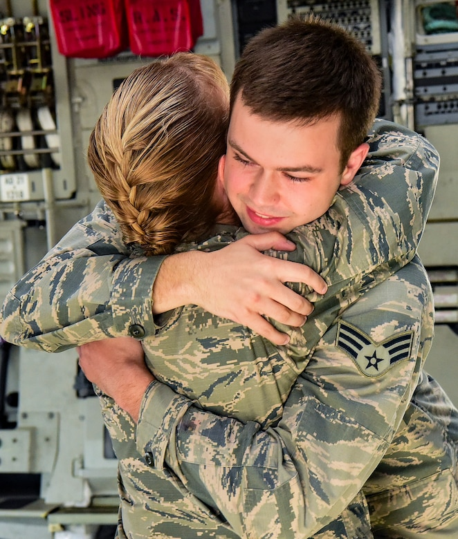 Senior Airman Cody Rupp, 628th Communications Squadron cyber-systems administrator, hugs his mom, Lt. Col. Karen Rupp, 437th Aerial Port Squadron commander, after she performed his re-enlistment ceremony Aug. 21, 2018, at Joint Base Charleston, S.C. The occasion also doubled as a surprise when his mother gave him the good news he had achieved the rank of staff sergeant.