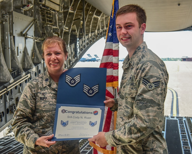 Lt. Col. Karen Rupp, 437th Aerial Port Squadron commander, presents her son, Senior Airman Cody Rupp, 628th Communications Squadron cyber-systems administrator, with a certificate of promotion to the rank of staff sergeant Aug. 21, 2018, at Joint Base Charleston, S.C. The occasion also doubled as a re-enlistment ceremony for Cody Rupp, which was performed by his mother.