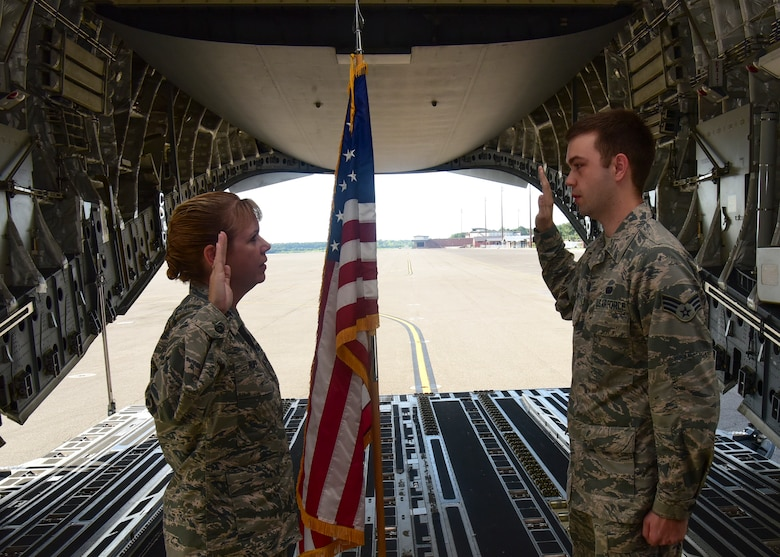 Lt. Col. Karen Rupp, 437th Aerial Port Squadron commander, performs a re-enlistment ceremony for her son, Senior Airman Cody Rupp, 628th Communications Squadron cyber-systems administrator Aug. 21, 2018, at Joint Base Charleston, S.C. The occasion also doubled as a surprise when his mother gave him the good news that he had achieved the rank of staff sergeant.
