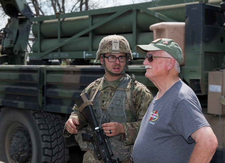 Army Spc. Caulin L. Gagne, a muliti-launch rocket system crewman assigned to the 197th Field Artillery Brigade, answers questions about a weapon system on Aug. 14, 2018 at a traiining site on Camp Grayling, Mich. Peter Dearness, the owner of New England Southern Railroad, visited the 197th FAB during their annual training as part of a tour with the N.H. Employer Support of the Guard and Reserve. (Photo by Staff Sgt. Kayla White, 157th Air Refueling Wing Public Affairs)