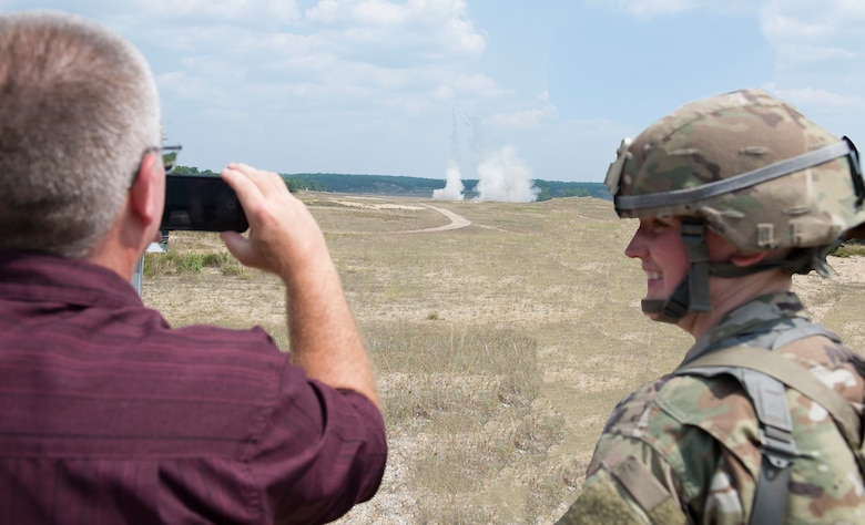 Spc. Heather M. Cote, a supply specialist assigned to the 197th Field Artillery Brigade, N.H. Army National Guard, smiles as her civilian employer, John Mercier records a HIMARS rocket launch demonstration on Aug. 14, 2018 at Camp Grayling, Mich. Mercier, and othe employers, visited their citizen-soldier employees during their annual training event as part of a tour with the N.H. Employer Support of the Guard and Reserve. (Photo by Staff Sgt. Kayla White, 157th Air Refueling Wing Public Affairs)