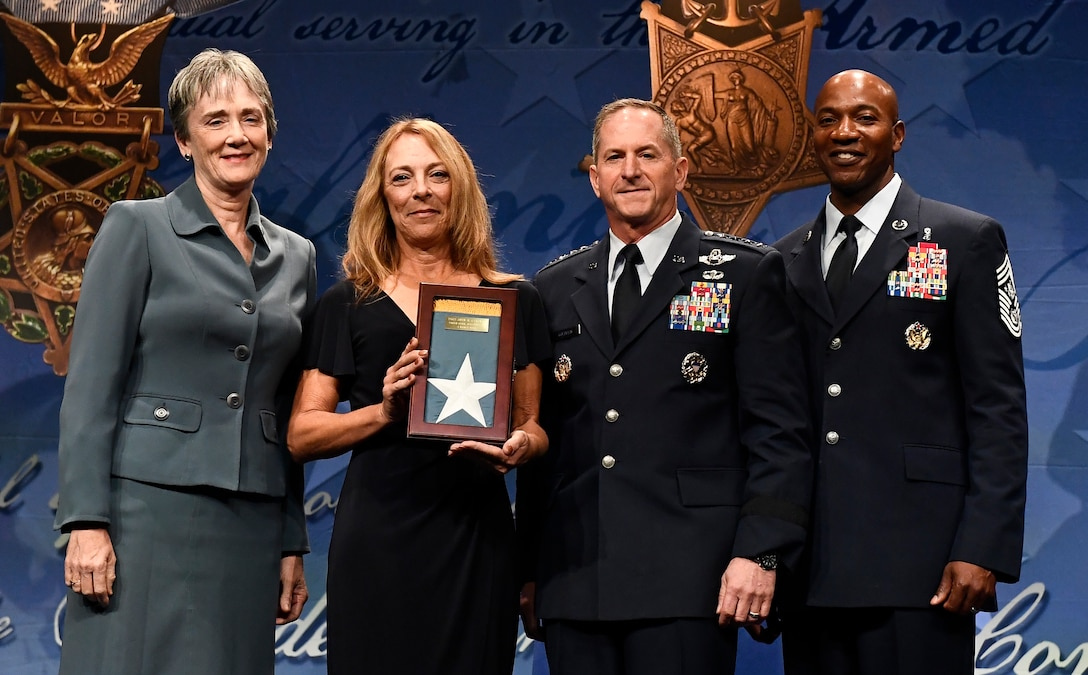 Secretary of the Air Force Heather Wilson, Air Force Chief of Staff Gen. David L. Goldfein and Chief Master Sgt. of the Air Force Kaleth O. Wright present the Medal of Honor Flag to Valerie Nessel, widow of Medal of Honor recipient Tech. Sgt. John Chapman, during Chapman's Pentagon Hall of Heroes induction ceremony at the Pentagon, in Arlington, Va., Aug. 23, 2018. Chapman was posthumously awarded the Medal of Honor for actions on Takur Ghar Mountain in Afghanistan March 4, 2002. An elite special operations team was ambushed by the enemy and came under heavy fire from multiple directions. Chapman immediately charged an enemy bunker through thigh-deep snow and killed all enemy occupants. Courageously moving from cover to assault a second machine gun bunker, he was injured by enemy fire. Despite severe wounds, he fought relentlessly, sustaining a violent engagement with multiple enemy personnel before making the ultimate sacrifice. With his last actions he saved the lives of his teammates. (U.S. Air Force photo by Staff Sgt. Rusty Frank)