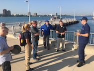 A member from the U.S. Coast Guard briefs Joint Task Force Civil Support members and other participants of the 2018 DoD Support of Civil Authorities (DSCA)/Chemical, Biological, Radiological and Nuclear (CBRN) Dense Urban Terrain Training Tactical Exercise Without Troops exercise Aug. 21-23 in Detroit, Mich. The Detroit River serves as an international border, as well as a means of transportation and commerce and would be significantly affected during a disaster. The task force members were among the 150 participants from more than 50 organizations of the interagency, to include local, state, federal and international partners. They gathered to increase their readiness for the CBRN mission with a focus on operating in a dense urban environment. Detroit is an inland seaport and handles traffic from all over the world by way of various connecting waterways and so afforded the training attendees with the opportunity to consider the challenges of responding to a DSCA event by water. The training was held by the 46th Military Police Command, Michigan Army National Guard, Command and Control CBRN Response Element – Bravo and also included training within the city landscape. (Official DoD photo by Air Force Lt. Col. Karen Roganov/released)
