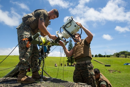 Lance Cpl. Justin Simmons, left, and Lance Cpl. Austin Ruckle, right, both field radio operators with 7th Communication Battalion, III Marine Expeditionary Force Information Group remove the free space optic system from a tactical elevated antenna mass at Camp Hansen, Okinawa, Japan, Aug. 17, 2018.
