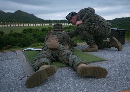 Lance Cpl. Timothy Larrigan, a range coach from Headquarters Battalion, 3rd Marine Division, gives advice to a fellow Marine during annual rifle range qualification on Camp Hansen, Okinawa, Japan, August 20, 2018.