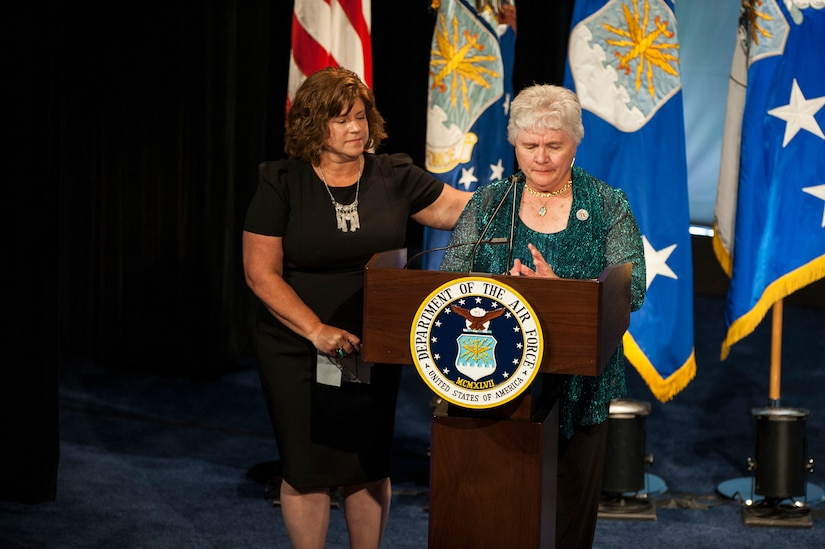 Terry Chapman, mother of Tech. Sgt. John Chapman, gives remarks about her son while her daughter, Lori Longfritz, comforts her during Chapman's Hall of Heroes induction ceremony at the Pentagon, in Arlington, Va., Aug. 23, 2018. Chapman was posthumously awarded the Medal of Honor for actions on Takur Ghar Mountain in Afghanistan March 4, 2002. An elite special operations team was ambushed by the enemy and came under heavy fire from multiple directions. Chapman immediately charged an enemy bunker through thigh-deep snow and killed all enemy occupants. Courageously moving from cover to assault a second machine gun bunker, he was injured by enemy fire. Despite severe wounds, he fought relentlessly, sustaining a violent engagement with multiple enemy personnel before making the ultimate sacrifice. With his last actions he saved the lives of his teammates. (U.S. Air Force photo by Staff Sgt. Rusty Frank)