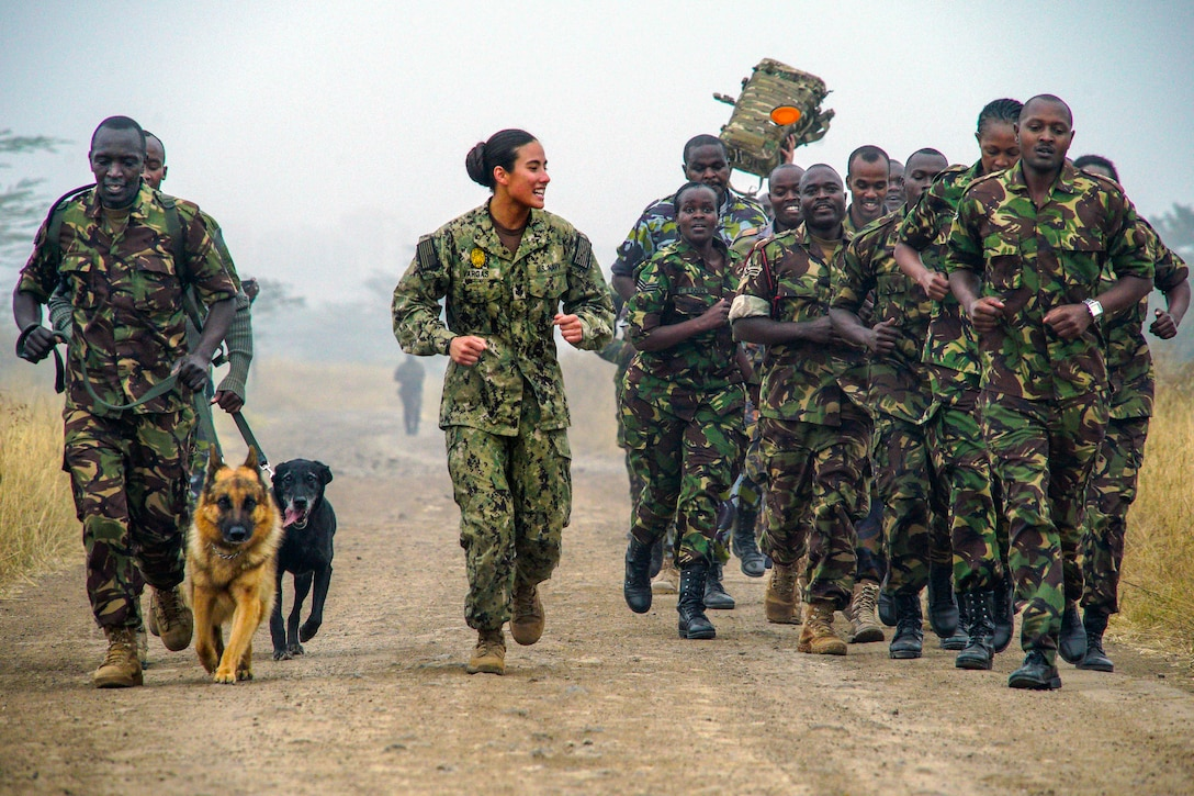 A sailor runs with a group of Kenyan service members