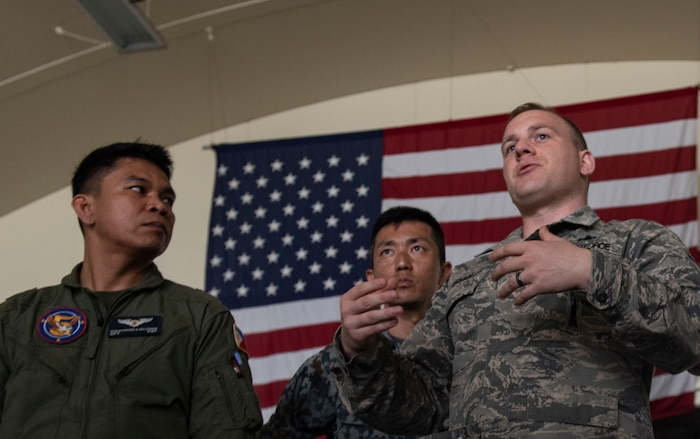U.S. Air Force Master Sgt. Benjamin Bouvy, 18th Maintenance Group loading standardization crew chief, briefs officers of allied and partner nations about the logistics of loading munitions to an F-15 Eagle during the 2018 Fighter Logistics and Safety Symposium Aug. 21, 2018, at Kadena Air Base, Japan. The symposium enabled air force officers from Australia, Indonesia, Japan, the Philippines, Singapore and Thailand to visit fighter support units assigned to the 18th Wing and interact with Airmen who support the fighter mission. (U.S. Air Force photo by Staff Sgt. Micaiah Anthony)
