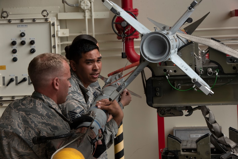U.S. Air Force Staff Sgt. Bryan Dann, left, 18th Maintenance Group weapons lead crew chief, Tech. Sgt. Jairek Kahai, 18th MXG loading standardization crew member, and Senior Airman Victoria Barsness, 18th MXG weapons lead crew member, demonstrate how to load munitions to an F-15 Eagle during the 2018 Fighter Logistics and Safety Symposium Aug. 21, 2018, at Kadena Air Base, Japan. The symposium enabled air force officers from Australia, Indonesia, Japan, the Philippines, Singapore and Thailand to visit fighter support units assigned to the 18th Wing and interact with Airmen who support the fighter mission. (U.S. Air Force photo by Staff Sgt. Micaiah Anthony)